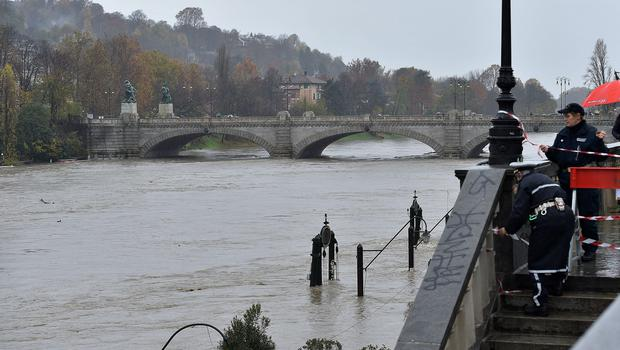 Municipality police seal off a stairway leading to the river banks as the water levels of the river Po rise, in the Murazzi area of Turin, northern Italy, Sunday, Nov. 24, 2019. Heavy rains and bad weather have been hitting most of Italy, causing river areas to flood and isolate hamlets in most part of northern Italy. (Alessandro Di Marco/ANSA via AP)