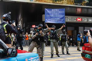 Police raised flags warning protesters to disperse (Kin Cheung/AP)