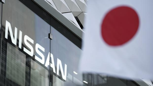 The Nissan logo is seen near a Japanese flag at the carmaker's showroom in Tokyo (Eugene Hoshiko/AP)
