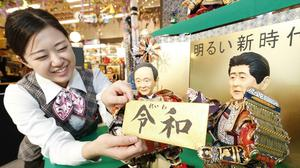 A shop worker arranges Japanese traditional dolls depicting Japanese chief cabinet Secretary Yoshihide Suga, left, and Japanese prime minister Shinzo Abe, right, holding the new era name Reiwa at Kyugetsu, a Japanese doll company, in Tokyo (Satoru Yonemaru/Kyodo/AP)