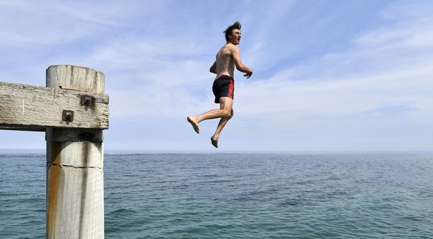 A swimmer jumps from the Port Noarlunga Jetty in an effort to cool off in Adelaide (AAP/AP)