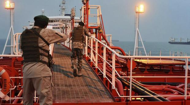 FILE – In this Sunday, July 21, 2019, photo, two armed members of Iran's Revolutionary Guard inspect the British-flagged oil tanker Stena Impero, which was seized in the Strait of Hormuz on Friday by the Guard, in the Iranian port of Bandar Abbas. The U.S. airstrike that killed a prominent Iranian general in Baghdad raises tensions even higher between Tehran and Washington after months of trading attacks and threats across the wider Middle East. (Morteza Akhoondi/Mehr News Agency via AP, File)