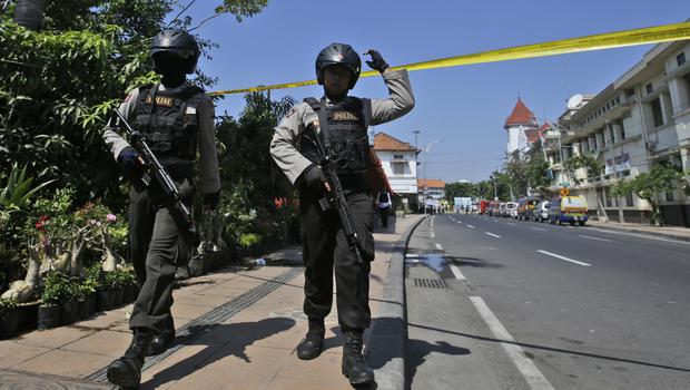 Officers near the police HQ after an attack in Surabaya (Achmad Ibrahim/AP)