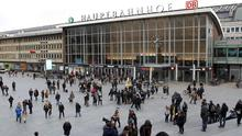 People walk across the square in front of the main station in Cologne, Germany (AP)