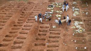 Cemetery workers bury victims of coronavirus at a cemetery in Sao Paulo (AP/Andre Penner)