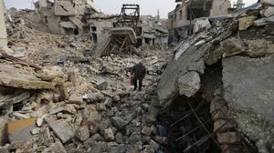 A resident walks amid the rubble in the once rebel-held Jalloum area of eastern Aleppo (AP)