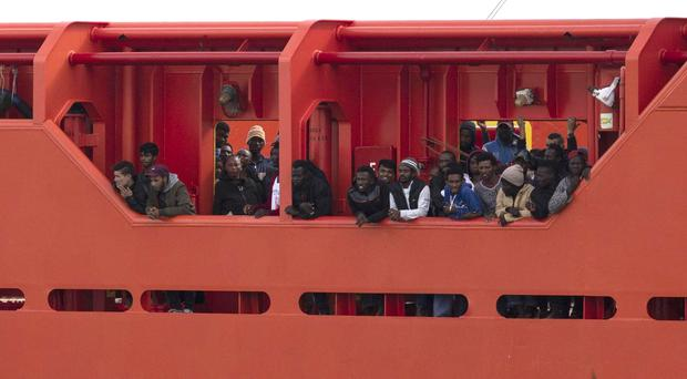Migrants wait to disembark from the Asso Trenta as it reaches the Sicilian port of Pozzallo (Francesco Ruta/ANSA/AP)