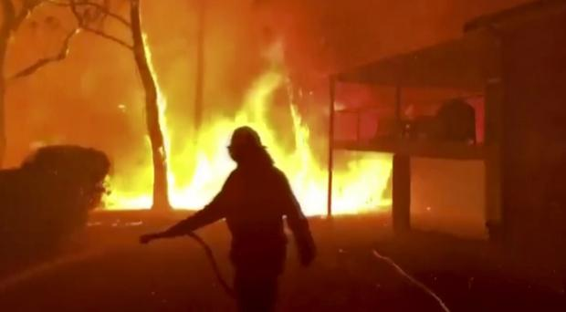 Australia's navy has been sent to evacuate people trapped in communities ravaged by the fires (Twitter@NSWRFS/AP)