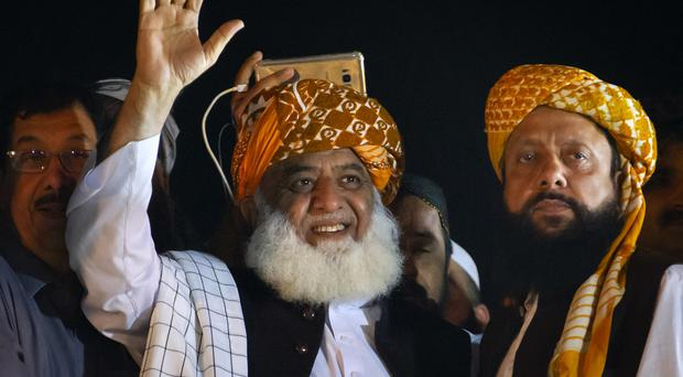 Firebrand cleric Maulana Fazlur Rehman, centre, waves to his supporters during an anti-government march (AP)