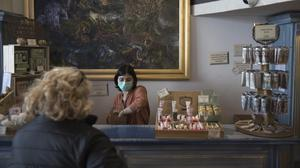Julie Dinot wears a mask as she attends to customers at the Savonnerie de la Licorne shop in Marseille (Daniel Cole/AP)