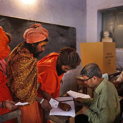 Indian Hindu holy men wait to cast their votes, in Haridwar (AP)