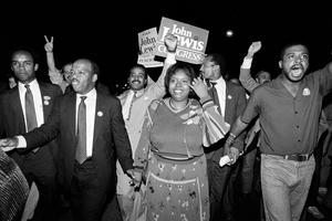 John Lewis, front left, and his wife Lillian lead a march of supporters from his campaign headquarters to an Atlanta hotel for a victory party after he defeated Julian Bond in a 1986 runoff election for Georgia's 5th Congressional District seat in Atlanta (Linda Schaeffer/AP)