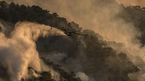A firefighting airplane drops water on a hill near the area of Kehries (Petros Giannakouris/AP)