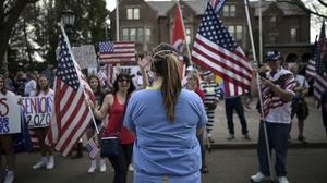 A woman who said she was a nurse counterprotests at a demonstration to open up the state of Minnesota, in the US (Aaron Lavinsky/Star Tribune/AP)