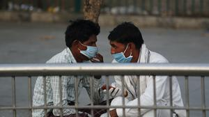 Relatives of admitted patients wearing face masks as a precaution against coronavirus talk outside a hospital in New Delhi, India, Thursday, June 18, 2020. India is the fourth hardest-hit country by the COVID-19 pandemic in the world after the U.S., Russia and Brazil. (AP Photo/Manish Swarup)