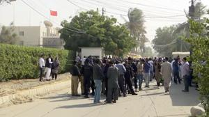 Security officials gather outside the compound of the Chinese Consulate (AP)