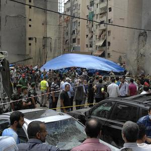 Security forces and civilians stand at the scene of the bombing (AP)