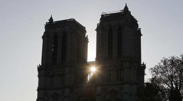 The sun rises between the two towers of Notre Dame cathedral after fire devastated the building (AP)