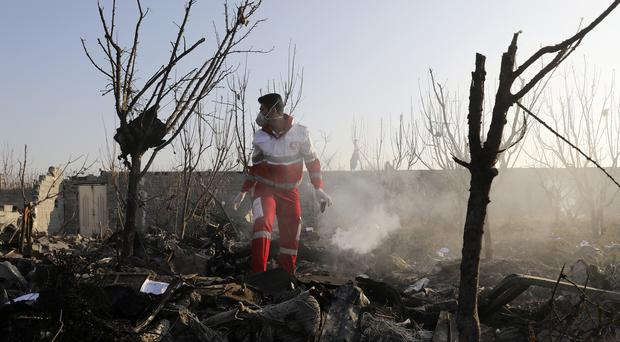A rescue worker searches the scene where a Ukrainian plane crashed in Shahedshahr, south west of Tehran (Ebrahim Noroozi)