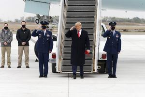 President Donald Trump salutes as he steps off Air Force One (Miguel Roberts/AP)