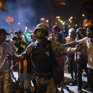A policemen walks away from demonstrators after trying to negotiate peace near the Mineirao stadium (AP)