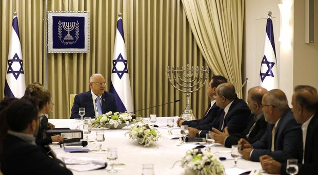 Israeli president Reuven Rivlin, centre, has held two days of crucial talks with party leaders before selecting his candidate for prime minister (Menahem Kahana/Pool via AP)