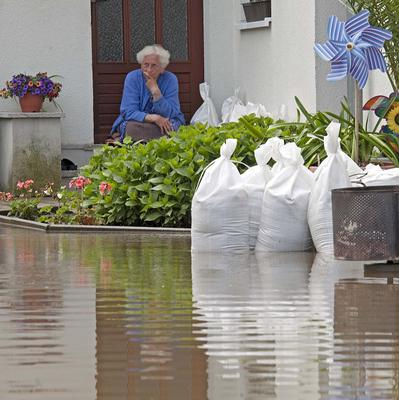 A woman sits in front of her house enclosed by the floods of the River Elbe in the village of Kreinitz near Riesa, eastern Germany (AP)