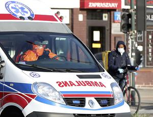 An ambulance passes a cyclist in Warsaw, Poland, on Saturday. While Poland has far fewer Covid-19 cases than other European countries such as Italy and Spain, its numbers are on the rise (Czarek Sokolowski/AP)