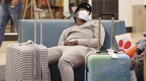 An airline passengers wears a mask in the terminal area of Orlando International Airport (Stephen M.Dowell/Orlando Sentinel via AP)
