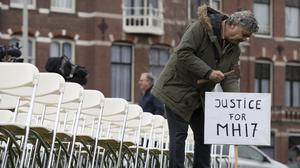 Rob Fredriksz, who lost his son Bryce and his girlfriend Daisy in the MH17 crash, places a sign next to 298 empty chairs opposite the Russian embassy in The Hague, Netherlands (Peter Dejong/AP)