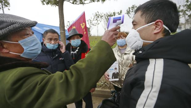 A government worker takes the temperature of a passer-by at a checkpoint in Suining in south-western China's Sichuan Province (Chinatopix/AP)
