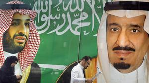 People walk past a banner showing Saudi King Salman, right, and his Crown Prince Mohammed bin Salman (AP)