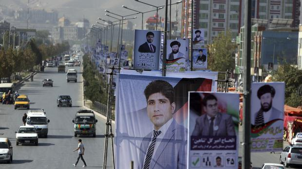 Election posters of parliamentary candidates are installed during the first day of campaigning in Kabul (Rahmat Gul/AP)