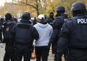 Police officers escort a person for an identity check in Berlin (Annette Riedl/dpa via AP)