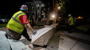 Workers secure a Confederate monument with straps after removing it from its base in Decatur, Georgia (Ron Harris/AP)