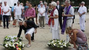 Relatives of tsunami victims lay white roses on the beach during a commemoration and religious ceremony for German, Austrian and Swiss victims in Khao Lak, Thailand (AP)