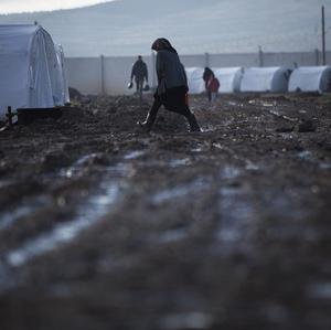 A woman walks through the mud in a refugee camp in Syria (AP)