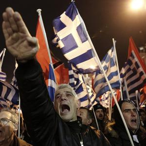 A Golden Dawn supporter makes a Nazi-style salute during a rally in Athens (AP)