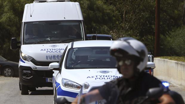 A motorcyclist police officer escorts and guards the police van carrying Army Captain Nicholas Metaxas from the court to the Cypriot central prison in the capital Nicosia (Petros Karadjias/AP)