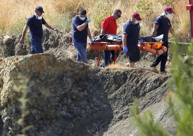 Cyprus police personnel carry a stretcher containing what is believed to be remains of a girl (Philippos Christou/AP)