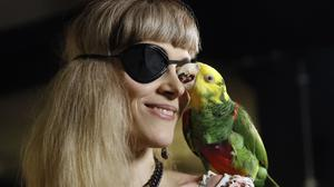 Pirate Party supporter Karen Pease arrives with her parrot named Mal at the election party in Reykjavik (AP)