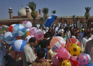 People buy balloons for their children after attending Eid al-Fitr prayer at historical Badshahi mosque in Lahore, Pakistan (K M Chaudary/AP)