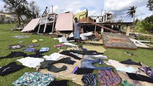 Clothes are seen laid out to dry as Adrian Banga surveys his destroyed house in Vanuatu's capital Port Vila (AP)