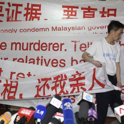 Chinese relatives of passengers on board Malaysia Airlines Flight MH370 arrange banners before speaking to reporters at a hotel in Subang Jaya, Malaysia (AP)