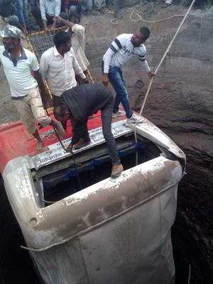 Rescuers pull the bus out of a well (News18 India/AP)