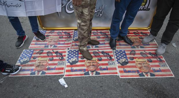 Mourners stamp on US flags with pictures of Donald Trump in Baghdad (Nasser Nasser/AP)