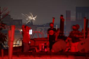 Fireworks explode over rooftops in Brooklyn (John Minchillo/AP)