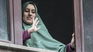Silvia Romano waves from a window of her home, in Milan, Italy (Luca Bruno/AP)