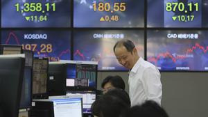 A currency trader smiles at the foreign exchange dealing room of the KEB Hana Bank headquarters in Seoul (AP)