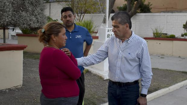 Coahuila Governor Miguel Angel Riquelme talks to a woman who said her son was missing after a gun battle between Mexican security forces and suspected cartel gunmen (Gerardo Sanchez/AP)